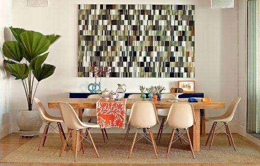 sala de jantar com quadro colorido e vaso de plantas.