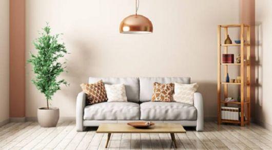 sala pequena com sofa clarinho e pedulo em tom rose gold.