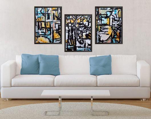 sala com sofa branco, almofadas azuis e quadros preto e branco.