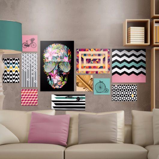 sala cinza, com sofá nude e almofadas e quadros coloridos.