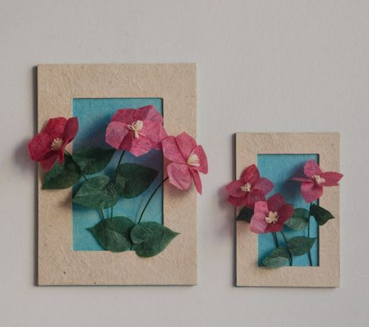 quadro decorativo com flores de plástico nas cores azul, verde e vermelho.