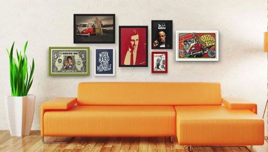sofa laranja com quadros decorativos vintage.