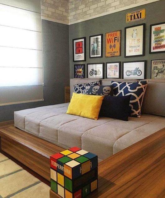 quarto cinza com paredes cinza chumbo e cama com almofadas coloridas.