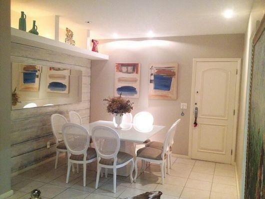 Sala de jantar clean branca com cadeira medalhão