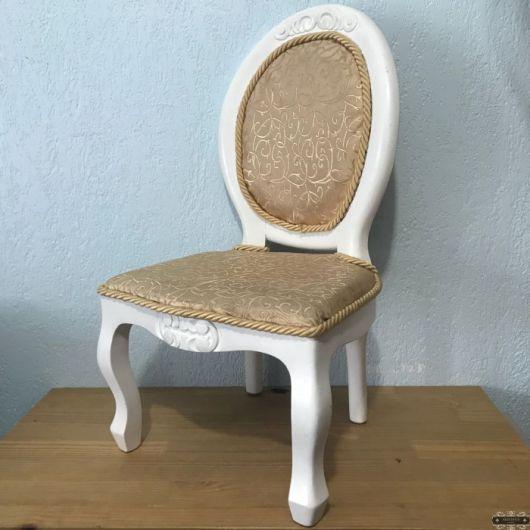 Cadeira com a estrutura em madeira branca e estofado bege