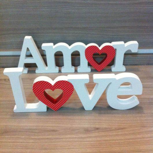 letras de mdf compoem palavra love e amor, estando pintadas na cor branco e vermelho.