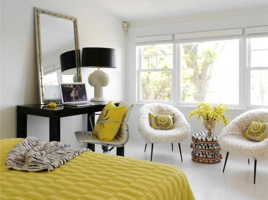 Em uma decoração colorida, a poltrona branca suaviza o resultado final