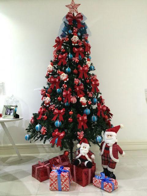 Árvore de Natal média com muitos laços vermelhos