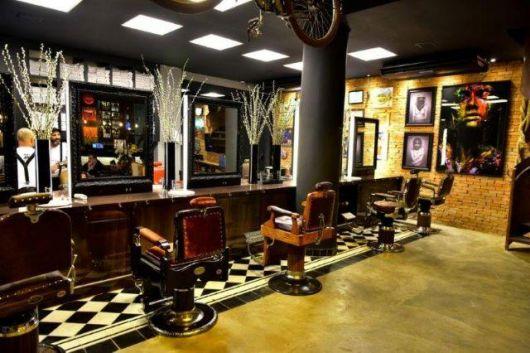 Pontos de luz na parede com quadros também ajudam a destacar a decoração da barbearia