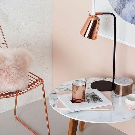 espaço para leitura com luminária de mesa rose gold