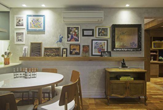 Sala de jantar e de estar com prateleira para quadros