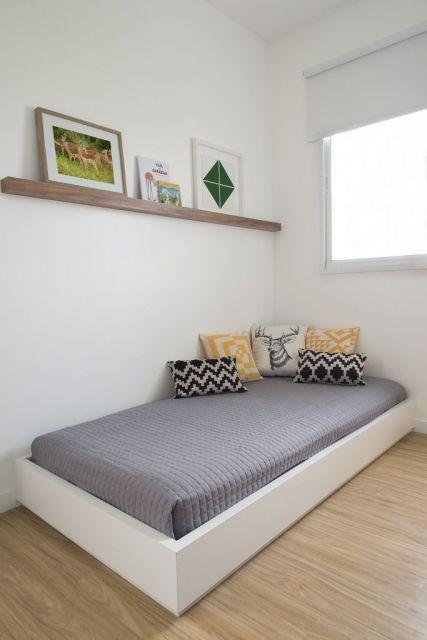 Quarto simples e moderno com prateleira em madeira para quadro
