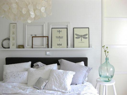 Prateleira branca para quadros acima da cama