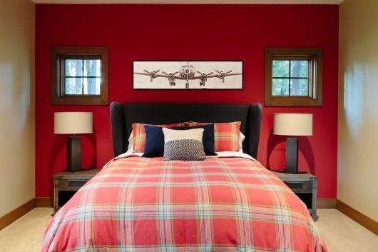 Parede vermelha e detalhes na roupa de cama