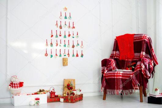árvore de natal de parede em sala com poltrona vermelha.