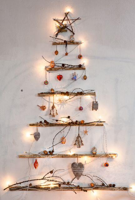 árvore de natal de parede com gravetos e pisca pisca em parede branca.