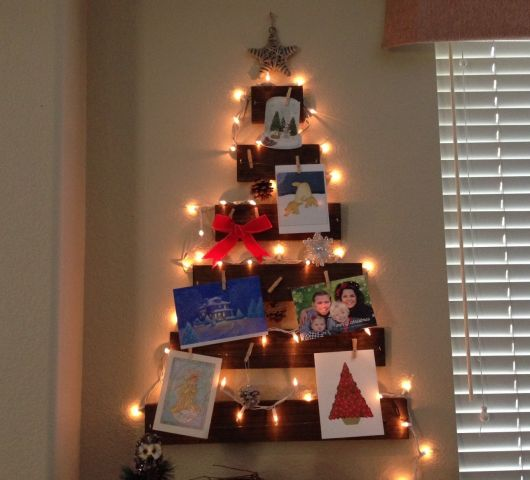 árvore de natal na parede de madeira com pisca pisca e fotos.