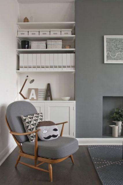 Sala com poltrona cinza e almofadas combinando.
