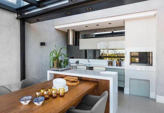 A mesa rústica se destaca na decor minimalista