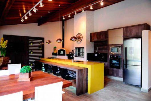 O balcão amarelo dá um toque moderno e arrojado à área gourmet moderna