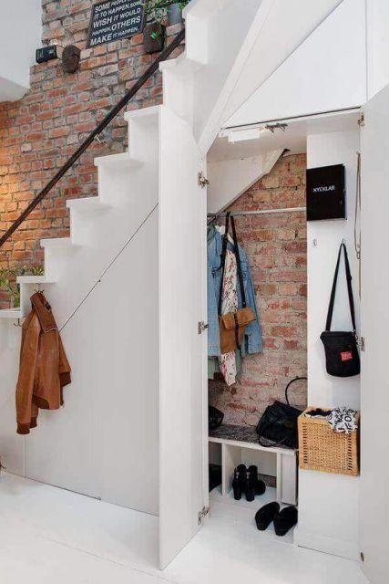 Armário planejado na parede rústica de tijolos para deixar casacos e bolsas
