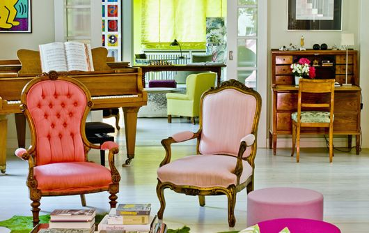 cadeiras decorativas nas cores rosa claro e vermelho com detalhes de madeira.