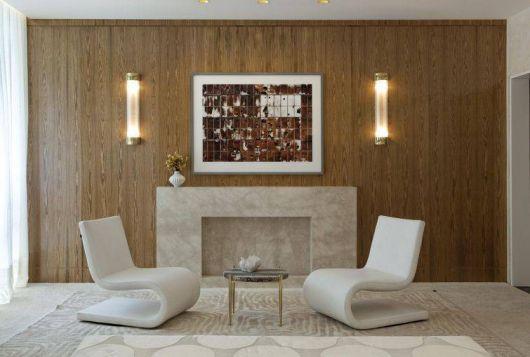 cadeiras brancas em ambiente com lareira e paredes de madeira marrom.