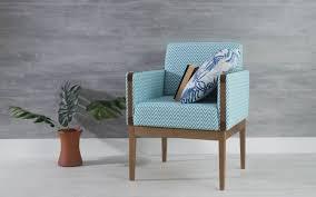 cadeira azul clara com detalhes de madeira e almofada estampada.