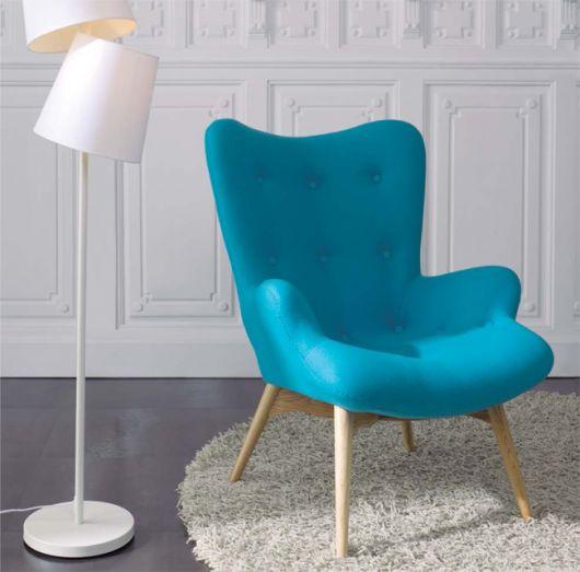 cadeira azul com pé em madeira em ambiente com tapete de pelinhos e abajour branco.