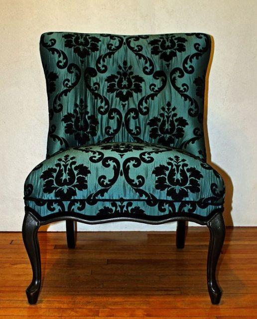 cadeira verde estampada com renda preta de flores.
