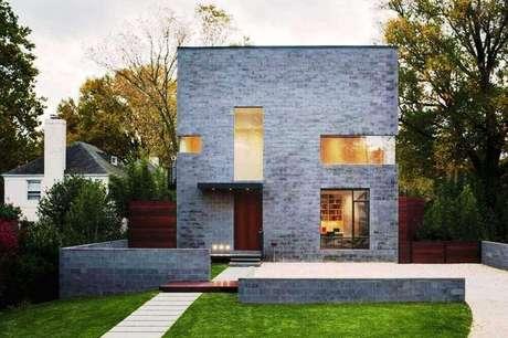 Entre as cores de casas modernas está o cinza, como nesse padrão com cimento queimado