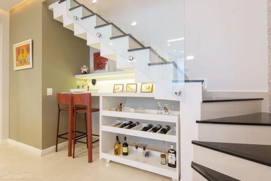 Modelo de bar criativo com móvel branco embaixo da escada