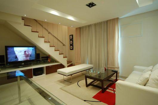 Colocar a TV embaixo da escada pode desocupar um espaço valioso em sua sala