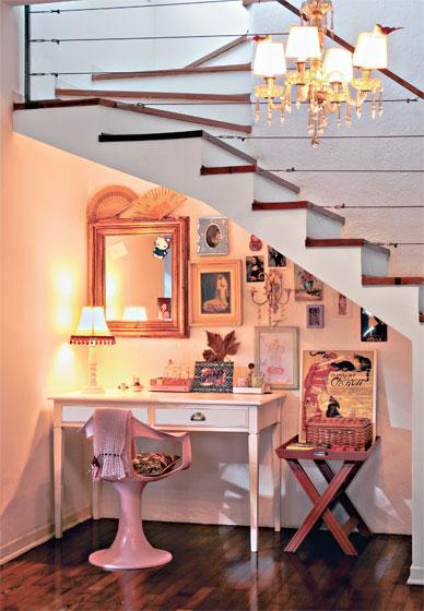 Decoração feminina embaixo da escada com quadros e espelhos