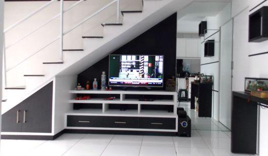Decoração embaixo da escada com rack branco e TV