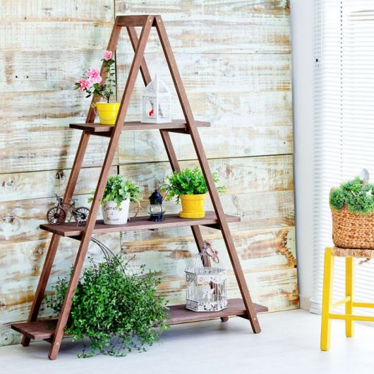 estante escada marrom com vasos de plantas.