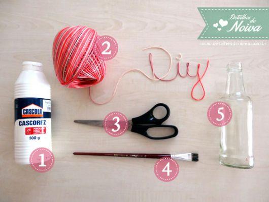 foto mostra tesoura, cola, pincel, lã e garrafa de vidro.
