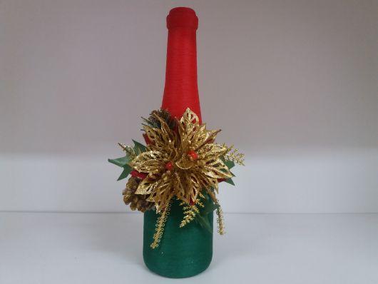 garrafa com barbante decorando nas cores vermelho e verde e adereço dourado.