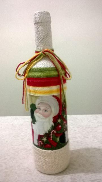 garrafa decorada com barbante branco, verde e vermelho com figura do papai noel.