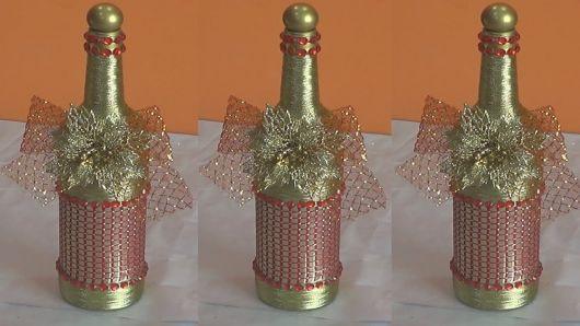 garrafas decoradas com tinha douradas e laços de fita natalinos douurados.