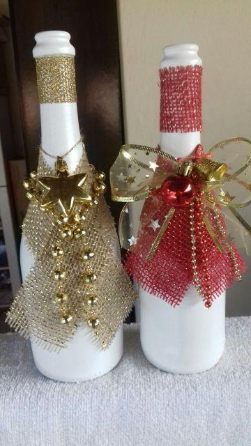 garrafas pintadas de branco com laços de fita vermelho e dourado.