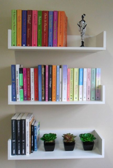 Diversos livros coloridos na prateleira junto a outros acessórios
