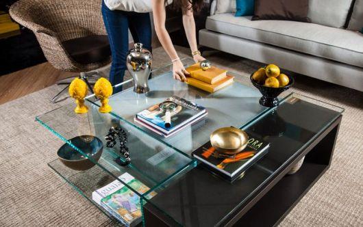 Na mesa de centro de vidro, livros decorativos e outros adereços