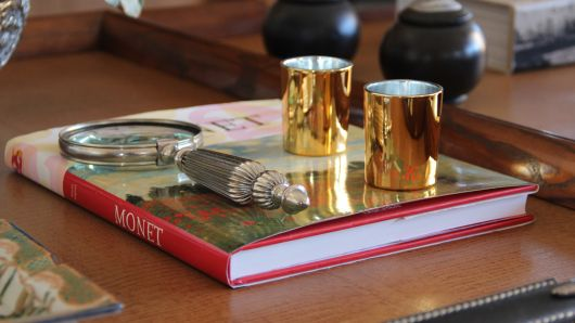 Um único livro sobre a mesa com uma lupa e copos dourados