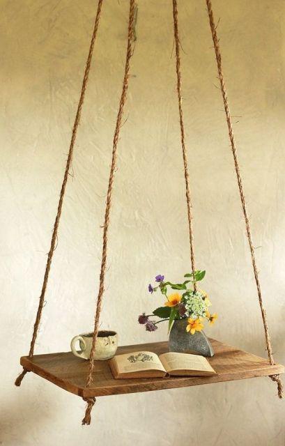 prateleira com corda apoiando xícara e vaso de flores.
