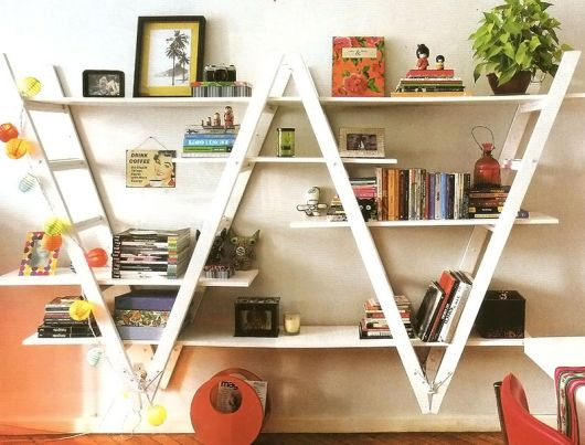 Prateleira de madeira branca de escada com livros, quadros e itens apoiados.