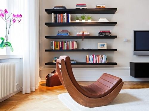 Prateleiras pretas em parede cinza e cadeira de couro.