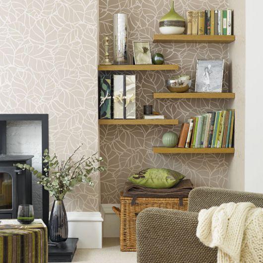 Sala com parede cor de areia e prateleiras de madeira amarelo queimado com livros apoiados.