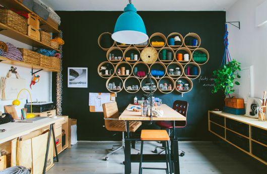 Prateleiras redondas em cozinha moderna com parede verde escuro.
