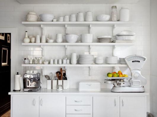 Imagem com prateleiras brancas, ármarios de cozinha na mesma cor.